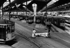 """Milan , 1986 - Inside the trolley depot  - workers with the advertising placard of """"Tonno Maruzzella""""   Milano , 1986 - All' interno di un deposito di tram - operai con la pubblicita' del """"Tonno Maruzzella"""""""